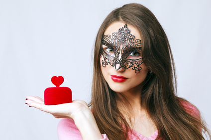 Young woman wearing a venetian mask with a heart shaped gift